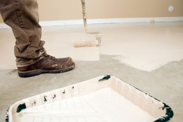 Painter painting garage floor.